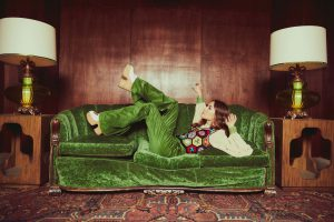 Lauren Daigle lying on her green velvet couch with one leg up